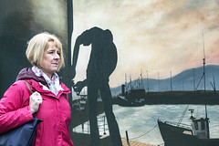 The lady and the mural (Frank Fullard) Tags: frankfullard fullard dingle lady mural candid street portrait nautical harbour kerry candis irish ireland fishing boat trawler pier red walkingtourist visitor