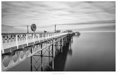 Llandudno Pier BW (John Joslin) Tags: pier boardwalk reflections reflection sea seaweed water ocean overcast outdoors outside sony sky clouds llundudno wales architecture longexposure monochrome blackwhite lifebuoy loxia2821 loxia a7rii