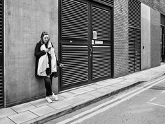 Northern Quarter 219 (Peter.Bartlett) Tags: manchester niksilverefex unitedkingdom people standing facade olympuspenf woman wall urban cigarette noiretblanc peterbartlett streetphotography girl cellphone candid uk m43 microfourthirds mobilephone bw monochrome sign blackandwhite city door england gb