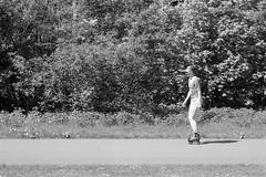Means of transport 2 (onemanifest) Tags: minoltaxd7 minoltamdrokkor85mm117 ilforddelta100 analog film monochrome blackwhite amsterdamwest kolenkitbuurt gentrification park shrubs transportation rollerskate woman sunny sunlight high contrast