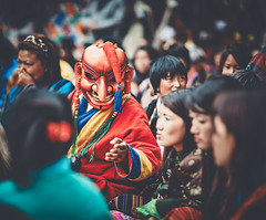 Bhutan: Atsara in their midst. (icarium.imagery) Tags: bhutan canoneos5dmarkiv travel buddhist captureone festival gasafestival gasatshechu localpeople maskdance masked rural spectators traditionalclothing traditionaldress traditional tshechu vibrant canonef85mmf12liiusm sundaylights