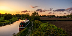 Evening by the canal (Peter Leigh50) Tags: newton harcourt canal grand union wistow water reflection reflections railway rural railroad towpath path sky cloud sunset boat narrow field farmland meridian train hedge fujifilm fuji xt2 landscape leicestershire