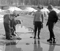 Fun with the melting ice (theirhistory) Tags: boy child children kid ice water hat jacket trousers wellies rubberboots play stick coat barrow boots