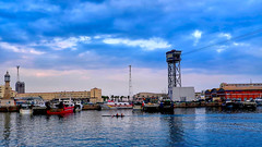 Rowing after sunset (Fnikos) Tags: port puerto porto harbour harbor rowing remo remar sea mar water waterfront sky skyline cloud building architecture sunset boat sailboat oar canoe people tower outdoor