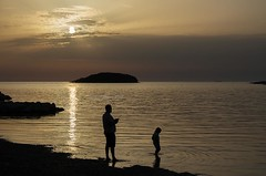 Silhouettes (Jumpin'Jack) Tags: small andabit bigger kid playing onthe beach witha remote controlled rc boat adriatic sea vrsar croatia island man child silhouette evening late afternoon sunset dusk sun ray reflection waves water monochrome