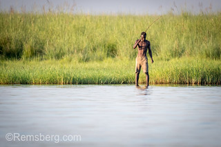 A Botswana man uses a pole and wire to fish in the waters of the Chobe River. Chobe National Park - Botswana