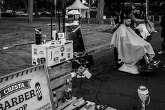 Barbieri in piazza (o.solemio) Tags: photo n°447 minoosolemio parco barbieri clienti poltrone da barbiere persone strada oggetti bottiglie spazzole pettini casse monocromo bianconero leicavlux