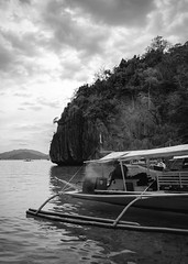 Philippines 8 (aviewthroughalens) Tags: boat travel trip explore food bbq smoke fish sky clouds light dark sea water mountains limestone rock trees wood bamboo guide float view landscape vignette philippines fujifilm xt2 1855mm acros