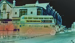 Ghost Bus - Summer 1974 (M C Smith) Tags: rt bus white ghost blue letters numbers symbols bank road cars car daf railings advertising negative black lamps driving suburbia buildings