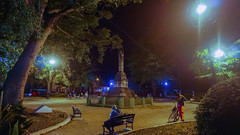 The truncated pillar monument dedicated to people who lost their lives fighting for freedom. Some while people coming into the park to use the wifi. Mártires Plaza, Barrio El Carmen, Santa Clara, Cuba 2018 (lezumbalaberenjena) Tags: cuba santa clara villas villa 2018 lezumbalaberenjena barrio carmen parque park plaza martires columna truncada mambises noche