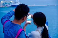 Amor  ♪♫ (Fnikos) Tags: port puerto porto harbour harbor waterfront cellphone mobilephone phone bokeh people dusk ship water sky outdoor