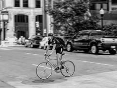 Passing Through (clarkcg photography) Tags: blackandwhite blackwhite bw bicycle tulsa street helmet petal wheel portrait action movement