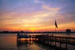 Racing, rhythms of the sun (Kathryn Louise18) Tags: canon florida kathrynlouise seascape centralflorida coastelflorida newsmyrnabeach sunset sunrise boat reflection dock flag landscape intercoastel roberthunterlyrics gratefuldeadlyrics