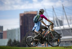 Parq In The Distance (Clayton Perry Photoworks) Tags: vancouver bc canada sun spring explorebc explorecanada skyline bcplacestadium people bike bicycle creeksidepark