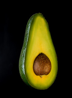 Half of avocado on black background. Clean vegetarian dieting concept.