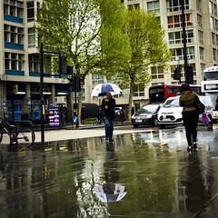 Black and White Umbrella, New Kent Road (London Less Travelled) Tags: uk unitedkingdom britain england london southwark elephantandcastle newkentroad rain reflection umbrella people urban city
