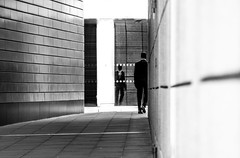 Me Or You? (DobingDesign) Tags: blackandwhite streetphotography man walkway contrast shadow lines paving walking footsteps reflection whichone lightandshadow geometric perspective london londonstreets sinister person architecture
