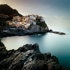 Village on the Rocks (One_Penny) Tags: italy cinqueterre photography tuscany canon6d rocks water sea ocean sky longexposure blur village houses manarola square squareformat sunrise light colors longshutterspeed ndfilter travel stones coast coastline waterfront view scenery city town architecture