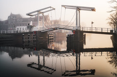The Gravestenen bridge, Haarlem (reinaroundtheglobe) Tags: haarlem haarlemmermeer noordholland nederland dutch netherlands water waterreflections canalhouses canal bridge gravestenenbrug fog morning sunrise nopeople buildings