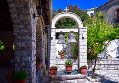 Panagia of Kassiopi (rustyruth1959) Tags: arch cross blooms flora plants paving tree exterior building placeofworship religiousbuilding flowerpots flowers plantpots churchbells latintravellers destroyed plunder venetians turks middleages virginmarychurch panagiaofkassiopi tamron16300mm nikond5600 nikon europe corfu kassiopi church bells wires terracotta leaves sky outdoor
