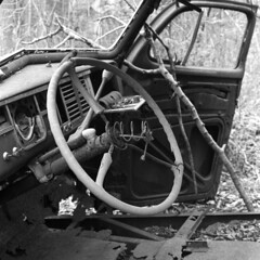 Steering Wheel and Dashboard of an Old Plymouth Decaying (pmvarsa) Tags: spring 2018 analog bw blackandwhite film 120 mf 6x6 mediumformat ilford ilfordfp4plus fp4 125iso nikonsupercoolscan9000ed nikon coolscan cans2s mamiya c33 mamiyac33 classic camera tlr twinlensreflex mood rust car chrysler plymouth decay abandoned derelict steering wheel dashboard trees leaves forest woods trail moraine art waterloo ontario canada