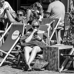 enjoying the spring sun (every pixel counts) Tags: 2018 berlin capital europa everypixelcounts blackandwhite 11 germany prenzlauerberg eu people street restaurant women smartphone móvil cellularphone celular mobile square fon mobiledevice deckchair city blackwhite bag daylight spring berlinalive