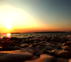 Sunset over beach rocks (michaeldantesalazar) Tags: rocks sunset lake pebbles sky nature sunsets sun shore beach beaches water canada depthoffield depth manitoba bokeh