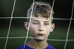 (Rebecca812) Tags: boy child portrait 11 blue green headandshoulders headshot people soccer futbol net goal pattern lookingthrough serious determination canon blondhair confident eyecontact rebeccanelson rebecca812 sports athlete