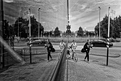 Split Screen (Alfred Grupstra) Tags: blackandwhite people urbanscene outdoors city citylife street bridgemanmadestructure sport bicycle monochrome cityscape cycling reflection