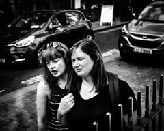 Siamese friends (Kieron Ellis) Tags: woman women friends talking walking railing sunglasses cars street candid blackandwhite blackwhite monochrome
