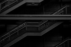 Multilevel parking garage exterior with close-up of metal stairs (Jim Corwin's PhotoStream) Tags: absence abstract architecturalcolumns architecture basement blackandwhite buildingfeature builtstructure car cars ceiling citylife concrete dark eerir electricity empty exterior foreboding gray illuminated incline indoors levels lightbulb metalstairs mysterious nature nobody parking parkinggarage parkinglot patterns photography railing repetition simplicity stairs trees underground