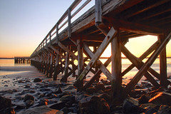 Reaching Out (SunnyDazzled) Tags: wooden pier fortfoster maine rocky shore sea ocean coast beach sand water colorful sunset reflective light horizon evening sunbeams glow coastal