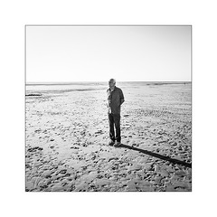 Il regarde toujours par delà l'horizon. (Scubaba) Tags: europe france pasdecalais noirblanc noiretblanc plage homme horizon mer sable carré blackwhite bw beach man sea sand square