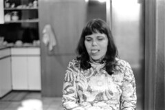 040371 05 (ndpa / s. lundeen, archivist) Tags: nick dewolf nickdewolf blackwhite monochrome blackandwhite 35mm film photographbynickdewolf bw april 1971 1970s boston massachusetts beaconhill familyhome 3mtvernonsquare people latenight kitchen woman brunette bangs maggie dress tongue stickingtongueout stickingouttongue stickinghertongueout may