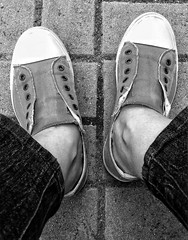 Resting feet in B & W. (arepax68) Tags: feet shoes sneakers canvasshoes black white greyscale jeans pavement