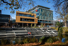 Red Stands Out (Jocey K) Tags: newzealand nikond750 christchurch cbd city architecture buildings trees shadows sky pathway river avon avonriver leaves autumn reflections water people rebuild steps terracedevelopment