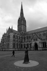 Walking Madonna [b/w] (Ian R. Simpson) Tags: walkingmadonna statue elizabethfrink cathedralclose lawn salisburycathedral cathedral cathedralchurchoftheblessedvirginmary cofe churchofengland anglican church grass tower spire building wiltshire england salisbury