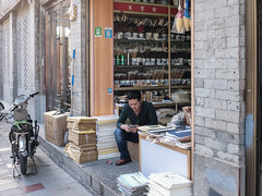 Texting in a caligraphy shop (Papaye_verte) Tags: shopkeeper merchant caligraphy boutique caligraphie magasin streetphotography marchand store shop xian chine