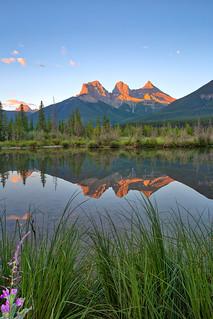 Three Sisters Mountain Range reflection in Policeman Creek, Canmore, Alberta