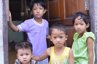 children in front of their house