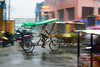 Man driving a pedal rickshaw in the rain in a Nepal border town (BryonLippincott) Tags: nepal asia asian centralasia pashupatinath nepali street streetscene rickshaw pedalrickshaw slowshutter motionblur panning moving shops driver hardwork tricycle transportation taxi rain wet downpour motion greentarp pedal pouring