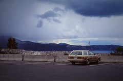 Car | Crater Lake, Oregon (1993) (Henry Hemming) Tags: oregonusa craterlake dark blue black sky skies brooding car auto alone lonely tourism carpark automobile 1990s nineties american wistful silent quiet tourist sightseer