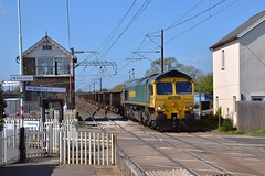 Freightliner 66548 arriving at Foxton, with a long line of mixed 30, 50 & 60 cubic metre box bogie wagons full of spoil, on the 09.18 working from Willesden Euroterminal for Barrington. 18 04 2018 (pnb511) Tags: traction locos locomotives diesels train track class66 levelcrossing signalbox railings sky blue