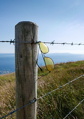 Abandoned shades (real ramona) Tags: shades sunglasses post wire barbed abandoned grass sea sky blue green lulworth