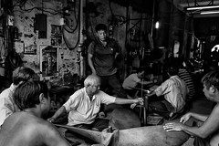 The old guy in the center mesures and shows the man standing up where to hit the propeller to give it a perfect shape. Once it's finished, this propeller will go to Japan (rvjak) Tags: mytho vietnam asia asie du sudest southasia old man vieil homme d750 nikon hélice propeller work travail black white noir blanc bw monochrome