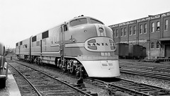 Santa Fe early EMC-GE A & B E-Units # 4L & 4A, that were delivered in April 1938, are seen spotted on a station track lead, Chicago, ca late 1930's (alcomike43) Tags: santafe atchisontopekasantafe railroads trains passengertrains diesels locomotives engines dieselengines diesellocomotives dieselelectriclocomotives emcge eunit aunit bunit 4l 4a e1 tracks rails ties rightofway yard stationtracks roadbed ballast conventionaljointedsectionrail tieplates anglebars spikes switch switchstand turnout vehicle car warbonnetpaintscheme buildings railroadfacilities photo photograph bw blackandwhite negative old historic vintage classic boxcars icedrefrigeratorcars nationalcarloaders