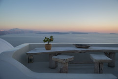 Whitewashed House on Cliff with Sea View, Wooden Table and Tiny Orange Tree during Sunset in Oia, Santorini, Cyclades, Greece (MilesAstray) Tags: balkans building cyclades europe greece island mediterranean architecture backdrop balcony bay bowl chair cliff coast dusk exterior greek historic holiday honeymoon house landscape nature oia orangetree outdoor panorama picturesque plant pot rock romantic santorini sea sky stone summer sun sunset table terrace tradition travel tree trunk view whitewashed wood