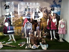 visions of Bavaria (SM Tham) Tags: europe germany munich neuhauserstreet steindltrachten traditional bavarian costume lederhosen dirndl clothes hats adults children mannequins shop window reflections glass shoes tankards countrysidescene mountains facade