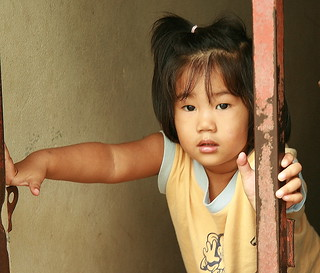 girl holding onto post