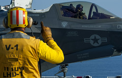 Aviation signals the pilot of an F-35B Lightning II aircraft on the flight deck.